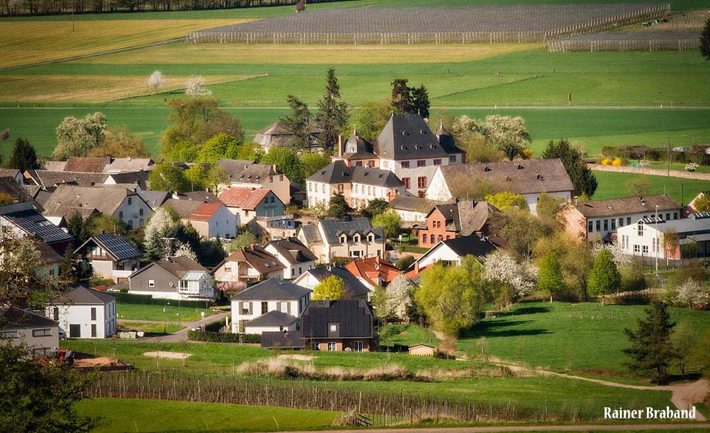 Blick auf das Schloss Bekond. Aufgenommen vom Berg in den Weinbergen. Ortskern von Bekond. Bürgerhalle, Kindergarten, Weinberge